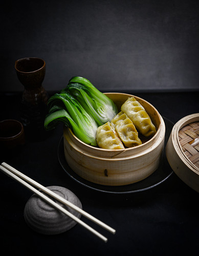 Steamed dumplings with pak choi in a bamboo steamer (Asia)