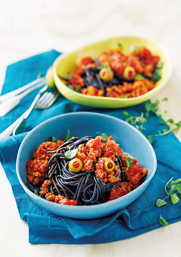 Black spaghetti with a minced meat sauce and olives