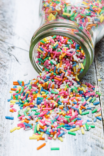Colourful sprinkles spilling out of a jar