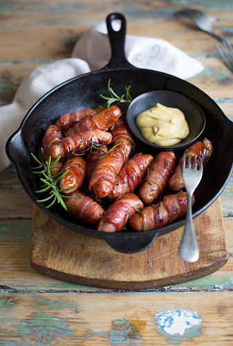 Bacon-wrapped chipolata sausages with mustard in a pan