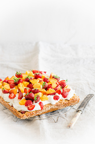 Peach and strawberry cake with mascarpone curd cream on a marzipan base