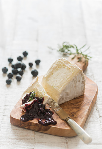 A piece of soft cheese (Delice de Bourgogne) with blueberry chutney on a wooden board