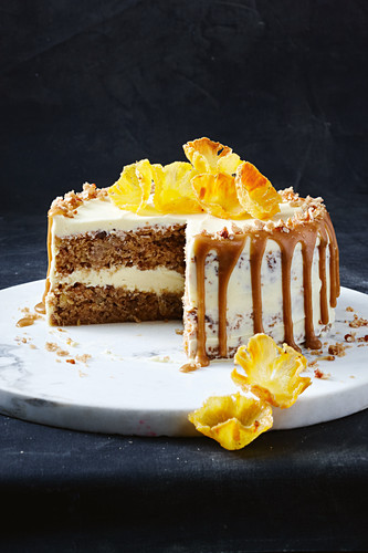 Hummingbird cake with pineapple, bananas, grated coconut, pecan nuts, caramel sauce, cream cheese, cinnamon and whisky