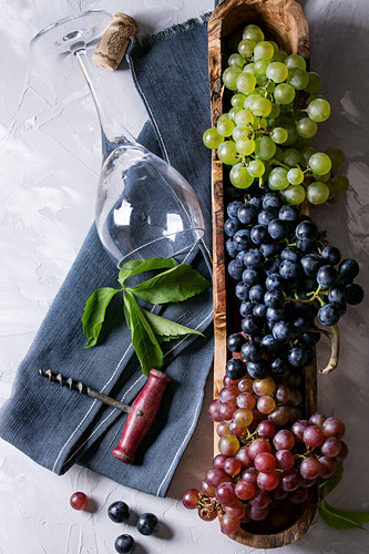 Variety of three type fresh ripe grapes dark blue, red and green in wooden bowl with empty laying wine glass, old corkscrew and green leaves