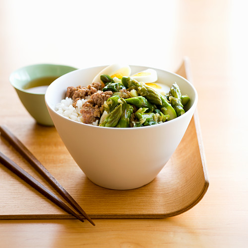 A bowl of rice with minced pork, asparagus and boiled egg
