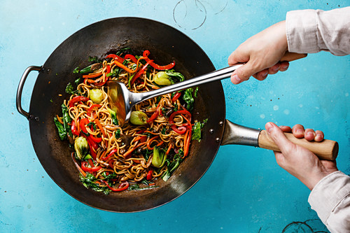 Udon stir fry noodles with oyster mushrooms and vegetables in wok pan and male hands on blue background