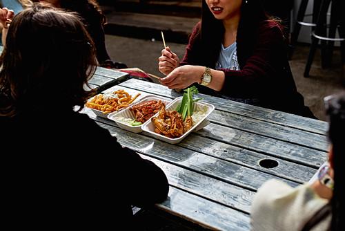 Street Food - Frauen essen Chicken Tikka Masala in Styroporschalen