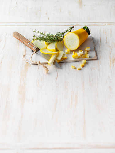 Sliced yellow courgette on a board with rosemary