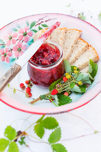 A jar of wild strawberry jam and slice of bread on an old enamel plate