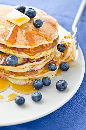 A Stack of Three Blueberry Pancakes with Maple Syrup and Orange Juice