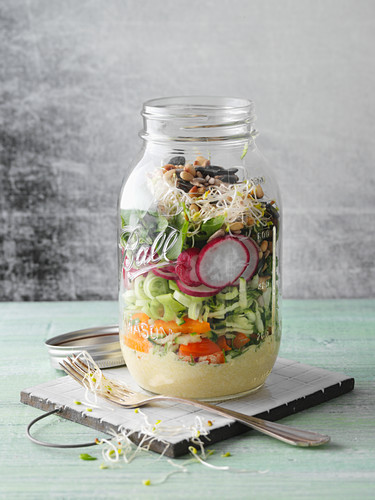Raw herbs with vegetables, tofu and shoots in a jar