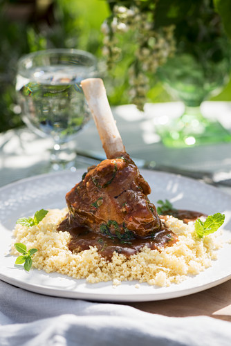A lamb shank with couscous on a summery table outdoors