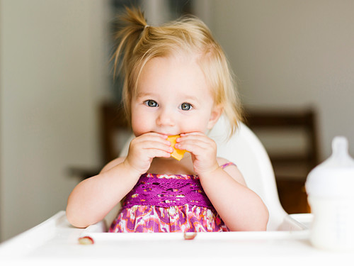 A little girl eating in a high chair