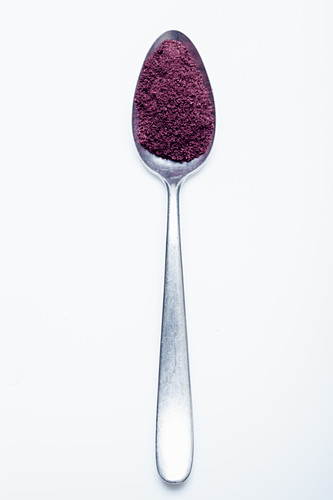 Acai berry powder on a spoon against a white background