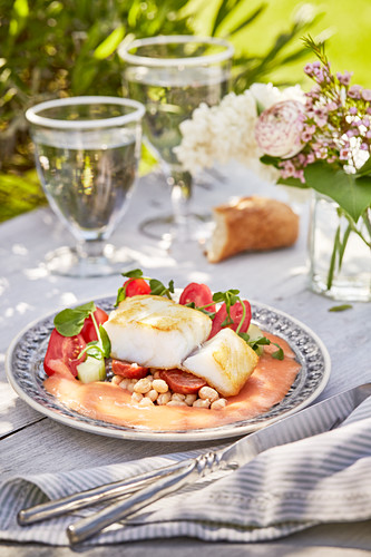 Fish fillets with tomato cream sauce on a summery table outdoors