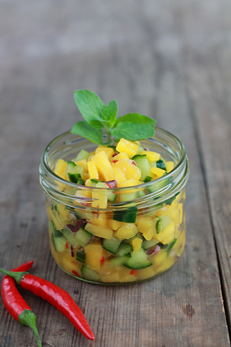 Mango salsa with cucumber and chilli in a jar on a wooden surface