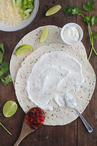 Huevos Rancheros being made: tortillas being spread with crème fraîché