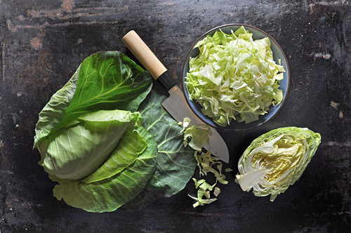 Pointed cabbage, whole, halved and sliced, in a ceramic bowl with a knife on a black baking tray