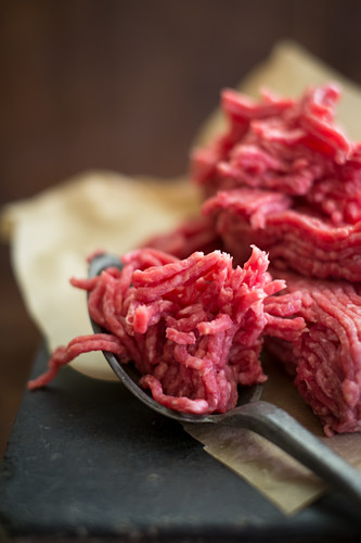 Fresh minced meat with a spoon on a piece of paper (close-up)