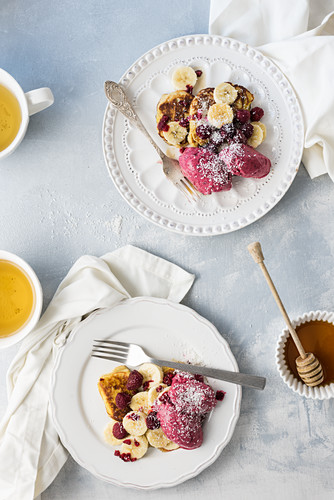 Pancakes with bananas, raspberries and maple syrup, served with tea