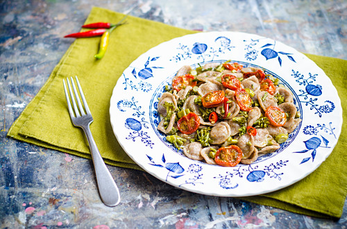 Wholewheat homemade orecchiette pasta with broccoli florets, cherry tomatoes, red chilli in a plate with blue decorations