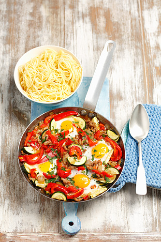 Minced meat with peppers, courgette and fried eggs served with pasta