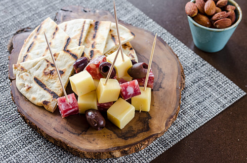 Meat charcuterie and cheese board with cubes of salami and soft cheese with kalamata olives and focaccia bread on a wooden board