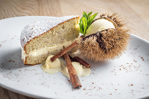 Chestnut cream sponge cake with cinnamon served with vanilla and chestnut ice cream garnished with fresh mint