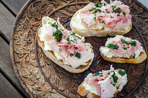 Bruschetta toasted sliced baguette, ciabatta and sourdough bread with spreadable soft cheese and ham drizzled with herbs