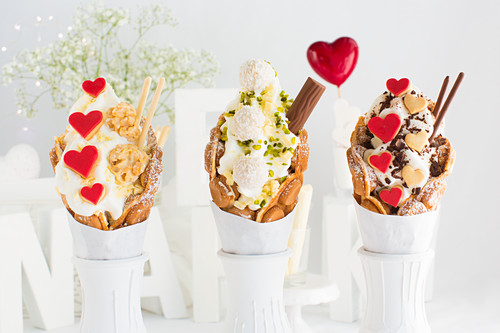 Three different bubble waffles with frozen yoghurt, heart-shaped biscuits and chocolate