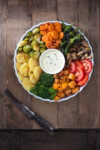 Vegan Buddha bowl with broccoli, duchess potatoes, sweet potatoes, mushrooms, Brussels, carrots, fried peperoni, tomatoes and herb sauce