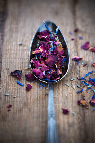 Dried, edible flower petals on a spoon