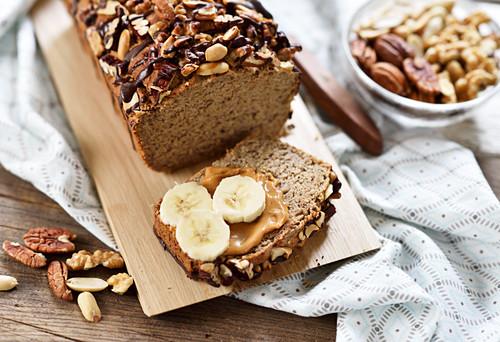 Veganes Triple-Nuss-Bananen-Brot mit Schokodrizzle, bestrichen mit Erdnussbutter, mit Bananenscheiben