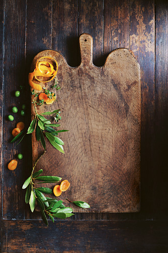 Olive leaves, orange peel and dried apricots on a wooden chopping board