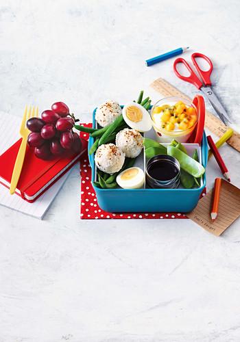 Avocado and sesame rice ball bento box with tropical yoghurt pots