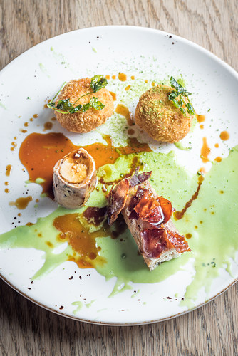 Roasted wild rabbit with crispy bacon and stuffed rice balls arancini and a sweet green pea sauce and gravy