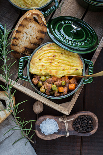 Shepherd's pie in a small cocotte with dark beer and bread