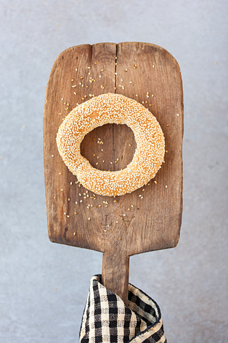 A sesame seed ring on a wooden paddle