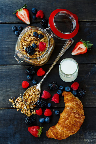 Breakfast ingredients: cereals, berries, yoghurt and a croissant (top view)