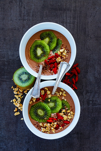 Tasty breakfast bowls of banana and chocolate smoothie, dessert, yogurt or milkshake topped with goji berries, kiwi fruit, seeds and oats