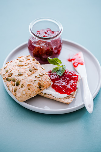 Quark and strawberry jam on a bread roll