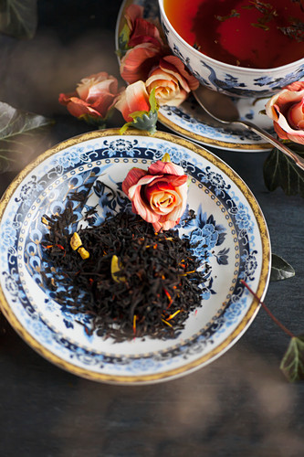 Tea leaves on a porcelain saucer, and a cup of black tea
