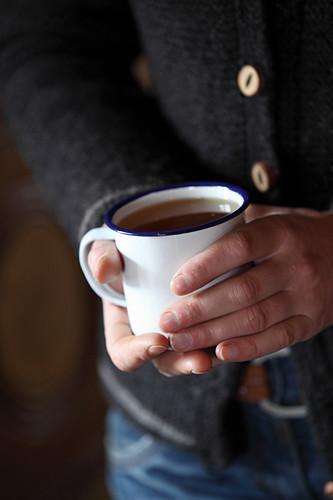 A person holding an enamel mug of tea
