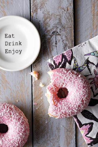 Angebissener Donut mit rosa Zuckerguss auf bunter Serviette