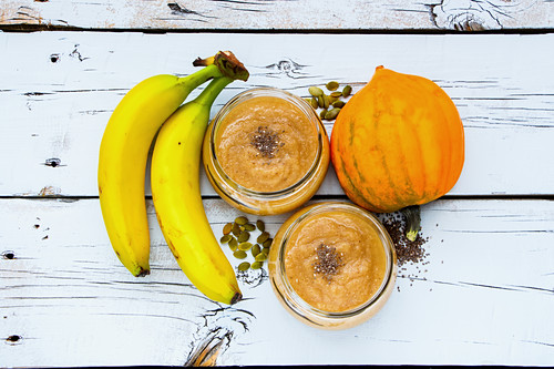 Glass jars of healthy pumpkin banana smoothie with chia seed and ingredients on white grunge wooden background