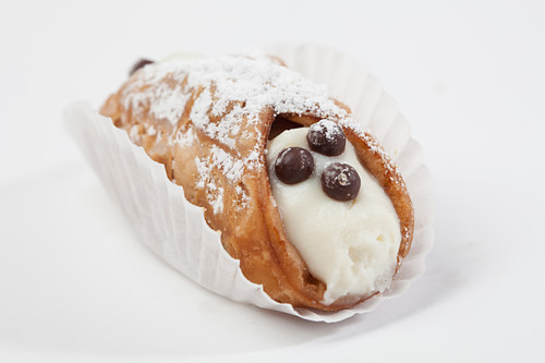 A sweet cannelloni filled with cream, in a paper case