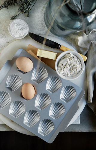 A Madeleine baking tin and ingredients (seen from above)