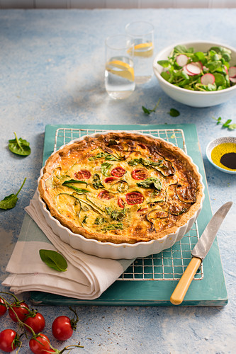 Spring quiche with cheese, spinach, tomatoes, courgette and spring onion