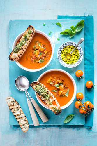 Tomato soup with salsa and grilled bread with basil pesto, view from above