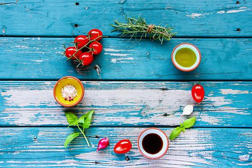 Food frame of olive oil, balsamic vinegar, vegetables, herbs and spices on turquoise vintage background